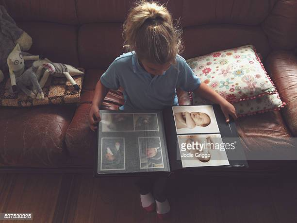 child looking through album of her own baby photos - childhood photo album stock photos and pictures