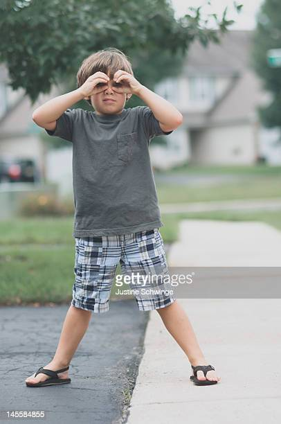 Child looking through pretend glasses