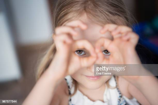 Child looking through the 'ok sign' gesture made with her fingers