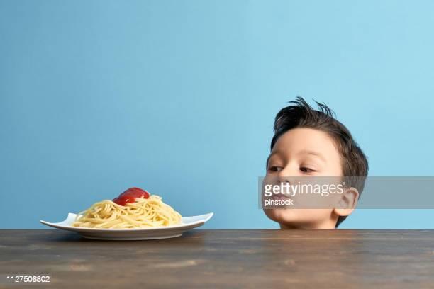 kind op zoek naar spaghetti - voeren stockfoto's en -beelden
