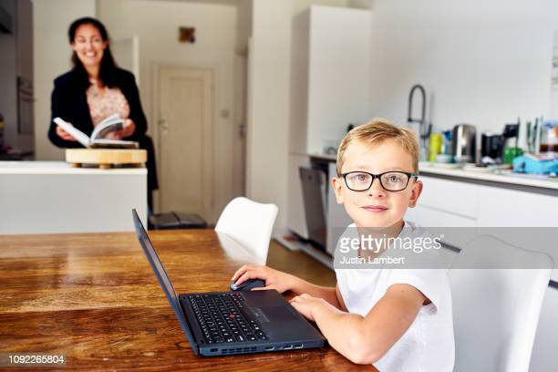 child looking up from his laptop sitting at the kitchen table - pre adolescent child stock pictures, royalty-free photos & images