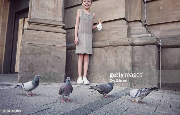 Child (10-11) looking worried as pigeons try to scavenge food off her