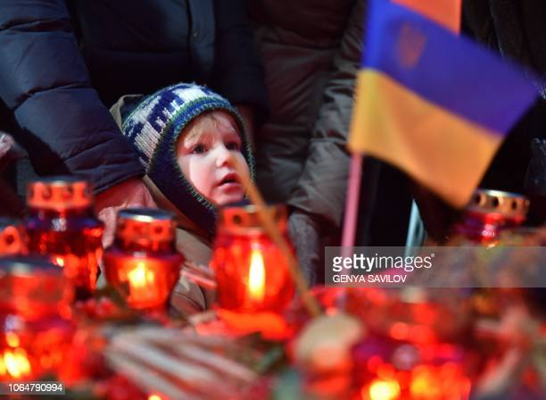 A child looks as people laying symbolic sheaves of wheat and lit candles during a commemoration ceremony at a monument to victims of the Holodomor...