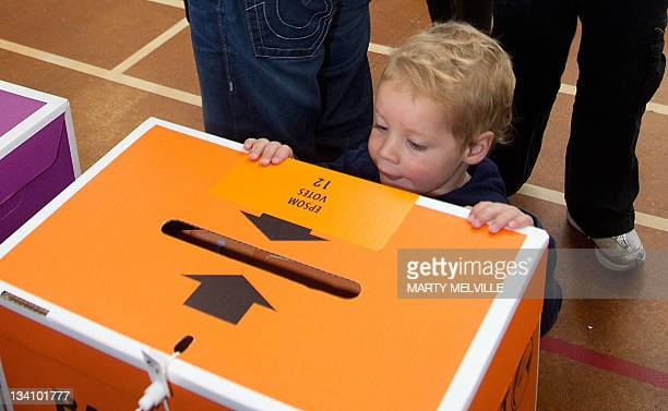 A child looks at a ballot box during the general election at a polling center in Auckland on November 26 2011 Polling opened across New Zealand in a...
