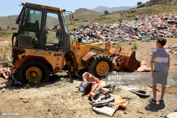 A child looks at a bulldozer amidst piles of discarded life preservers used by refugees in their attempted crossings from Turkey to Greece on the...