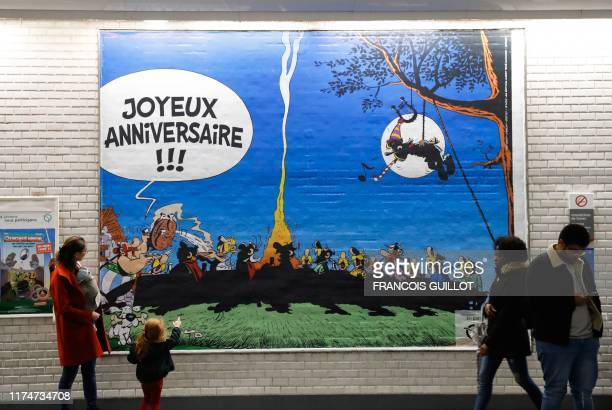 A child looks at a drawing especially designed to commemorate the 60th anniversary of France's famous comic characters Asterix and Obelix on October...