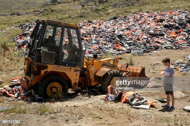 A child looks at a pile of discarded life preservers used by refugees in their attempted crossings from Turkey to Greece on the island of Lesbos on...