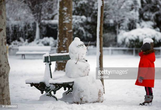 A child looks at a snowman at the Champs de Mars garden near the Eiffel Tower on February 7 2018 in Paris France After exceptionally heavy snow last...
