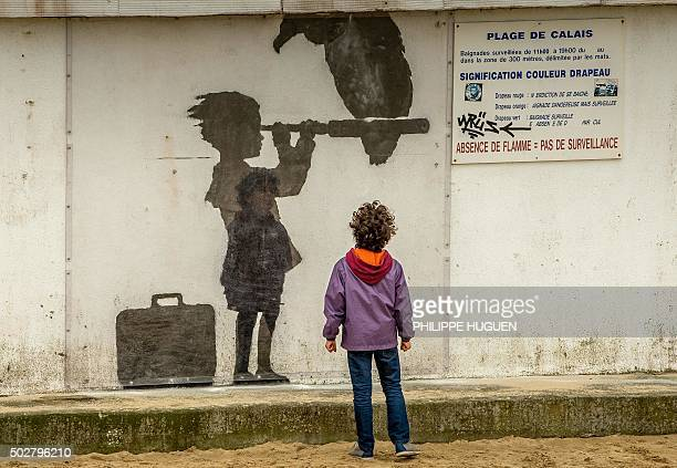 A child looks at an art piece protected by a plexiglass pane by British artist Banksy representing a child with a suitcase looking through a...