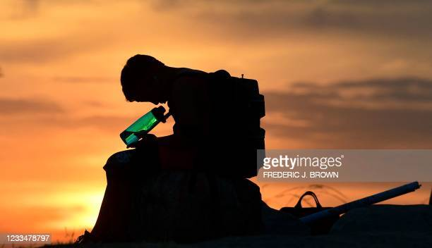 Child looks at his water bottle as the sun sets on June 15, 2021 in Los Angeles, California as temperatures soar in an early-season heatwave.