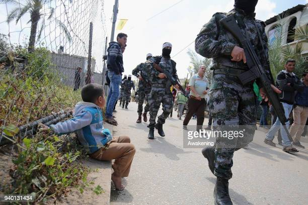 A child looks at Israeli forces while they intervene in the Palestinian protests as they gather at Israel's border near Khan Yunis district under the...