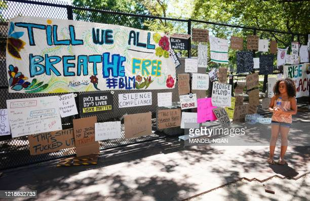 A child looks at posters and placards on the security fence on the north side of Lafayette Square near the White House in Washington DC on June 8...