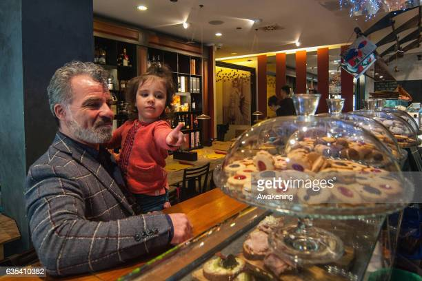 Child looks at some biscuits with her father for lunch in the Antonio Ferrari restaurant on February 15, 2017 in Padova, Italy. The restaurant offers...