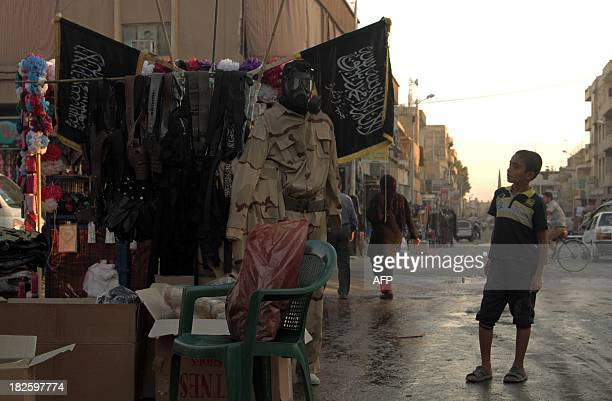 A child looks at stand selling military fatigue in the northern rebelheld Syrian city of Raqqa on October 1 2013 as violence continues to rage in...