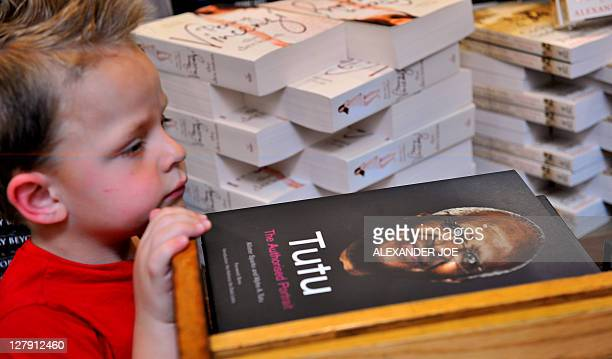 A child looks at the a book entitled 'Tutu The Authorised Portrait' at a bookstores in Johannesburg on October 3 2011 ahead of Desmond Tutu's 80th...