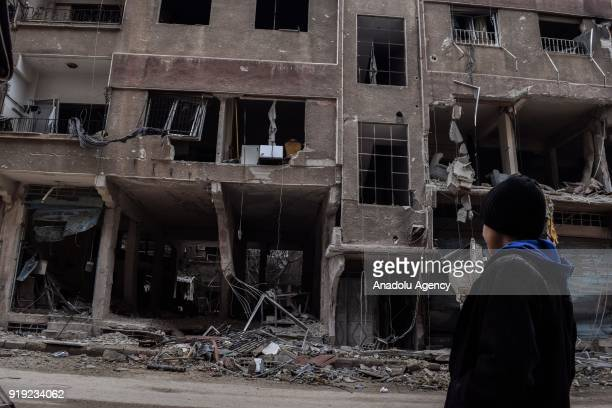 A child looks at the debris of buildings after Assad Regime's airstrikes and ground attacks to Harasta town in the besieged Eastern Ghouta in...