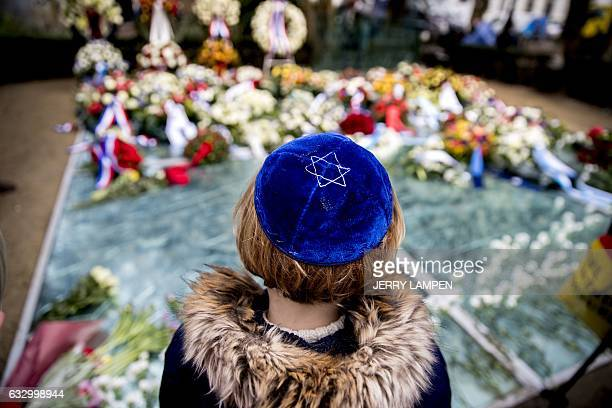 A child looks at the flowers that are placed at the Auschwitz monument in the Wertheimpark in Amsterdam on January 29 during International Holocaust...