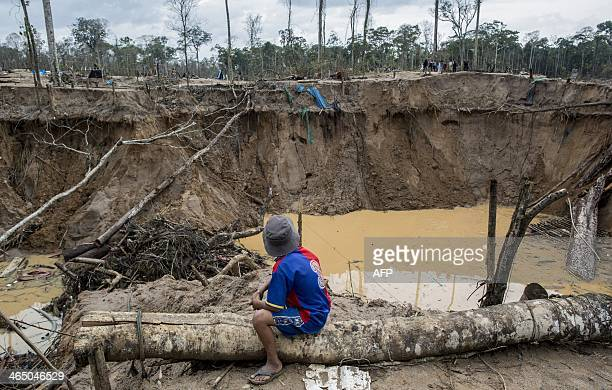 A child looks at the tailing produced by illegal gold mining in Mega 13 Madre de Dios region Peru on January 25 during a police operation AFP PHOTO /...