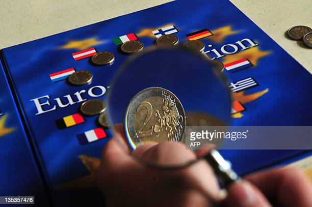 A child looks at two Euro coins as part of his collection on December 9 2011 in MilanAFP PHOTO / GIUSEPPE CACACE