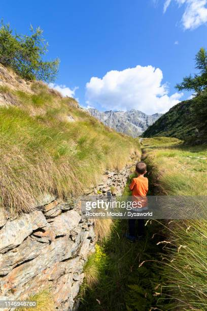 Child looks at war trenches, Valcamonica, Italy