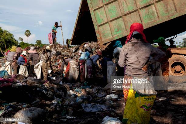 A child looks for recyclable material at the top of a pile of trash just dumped by the garbage truck while others look at the ground of the landfill...