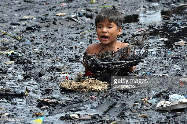 A child looks for salvageable materials while submerged in water filled with charred items and ash after a fire gutted a sprawling shanty town in...