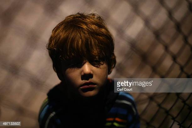 A child looks from behind a fence in a reception centre after making the crossing from Turkey to the Greek island of Lesbos on November 14 2015 in...