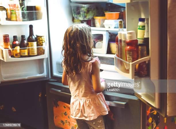 l'enfant regarde dans le réfrigérateur de famille désordonné - frigo humour photos et images de collection