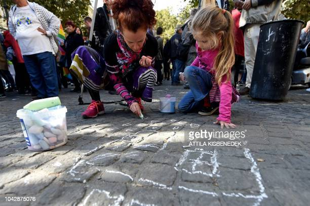 A child looks on as a woman draws with chalk a house on the pavement on the sidelines of a demonstration against the Hungarian government's housing...
