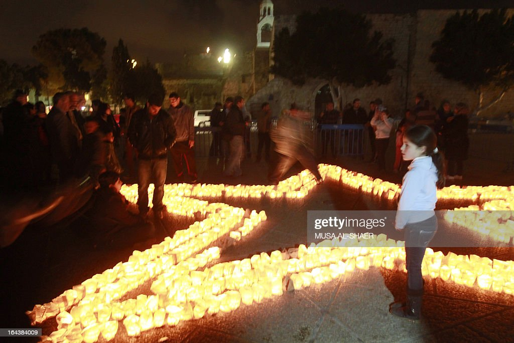 A child looks on as members of Palestine Wildlife Society outline the star of Bethlehem with candles at the Manager Square in front of the Church of the Nativity in the West Bank town of Bethlehem on March 23, 2013, to mark the Earth Hour for the first time in Palestine. Iconic landmarks and skylines were plunged into darkness as the 'Earth Hour' switch-off of lights around the world got under way to raise awareness of climate change.