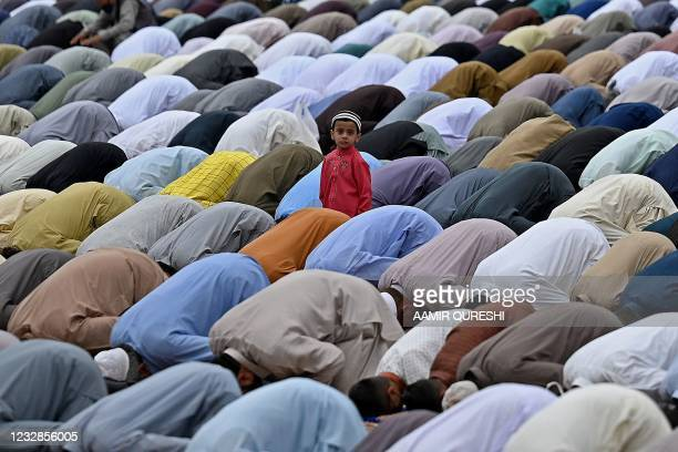 Child looks on as Muslim devotees offer special prayers on the occasion of Eid al-Fitr that marks the end of the holy month of Ramadan at Eidgah...