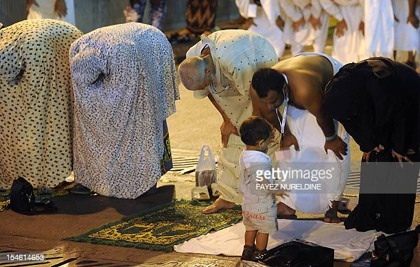 A child looks on as Muslim pilgrims perform evening prayers along a street close to the Grand Mosque in the holy city of Mecca on October 23 2012...