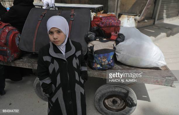 A child looks on as people board Syrian Red Crescent buses evacuating humanitarian cases from Douma Eastern Ghouta on the eastern outskirts of the...