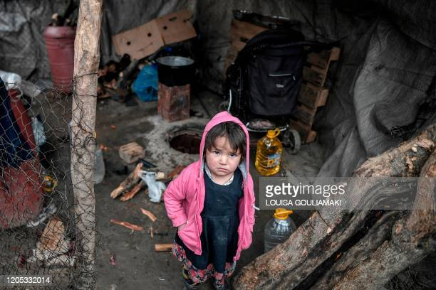 Child looks on from its family shelter at the overcrowded Moria migrant camp on the island of Lesbos, on March 5, 2020. - Greece's defence ministry...