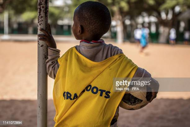 Child looks on on as other kids play football during a FIFA Grassroots schools program on January 15 2019 in Dakar Senegal