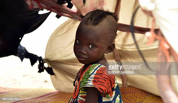 A child looks on under a makeshift tent in a camp in the village of Kidjendi near Diffa on June 19 2016 as displaced families fled from Boko Haram...