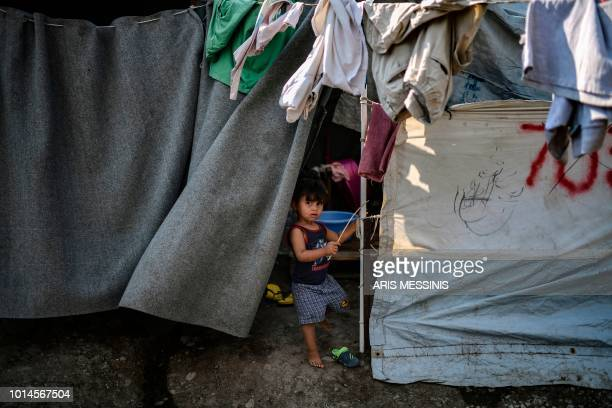 A child looks on while standing in a tent at a camp next to the Moria refugee camp in the island of Lesbos on August 5 2018