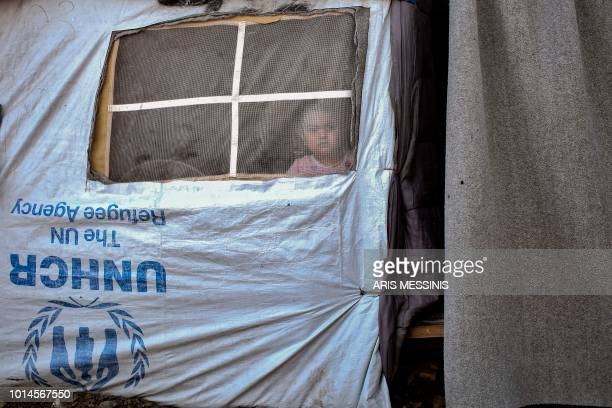 TOPSHOT A child looks on while standing in a tent at a camp next to the Moria refugee camp in the island of Lesbos on August 5 2018