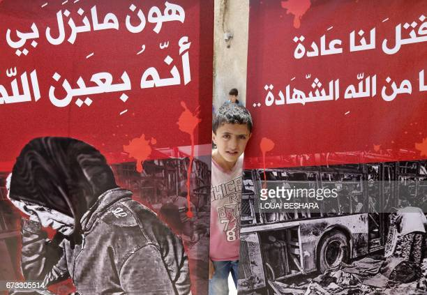 TOPSHOT A child looks out from behind posters during a funeral ceremony in the Sayyida Zeinab mosque on the outskirts of Damascus on April 26 for the...