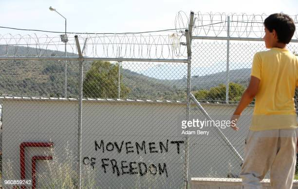A child looks over the Moria refugee camp on May 20 2018 in Mytilene Greece Despite being built to hold only 2500 people the camp on the Greek island...