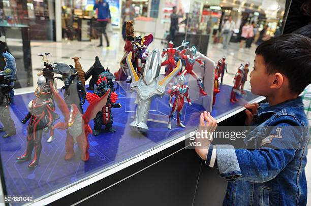 A child looks small Ultraman models displayed in a shopping mall on May 3 2016 in Shanghai China As part of an exhibition commemorating 50th...