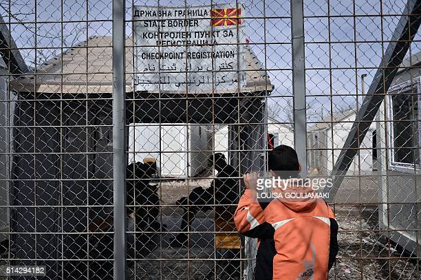 A child looks through a closed fence at the GreekMacedonian border near the village of Idomeni on March 8 where thousands of refugees and migrants...
