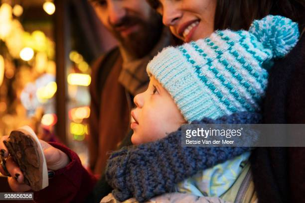 Child looks up at christmas ornaments at christmas market stall.