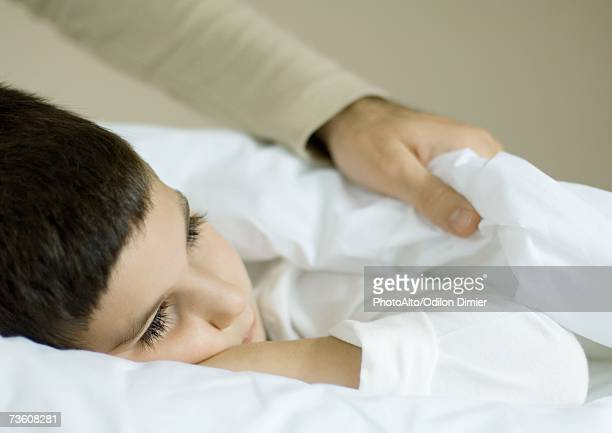 Child lying in bed, father pulling up covers