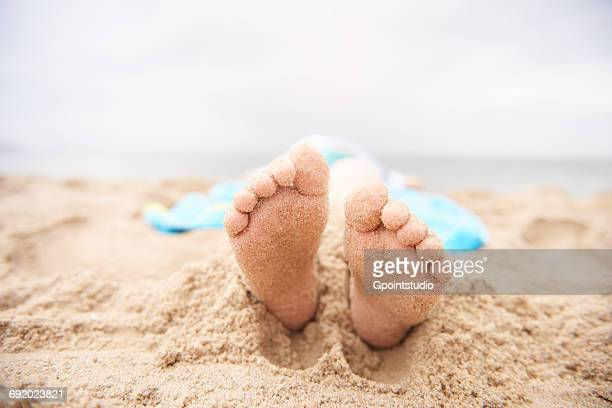 Child lying on sandy beach, view from feet