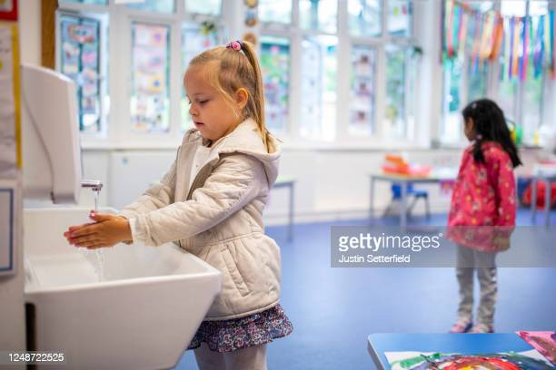 A child maintains social distancing measures while washing hands ahead of a lesson at Earlham Primary School which is part of the Eko Trust on June...