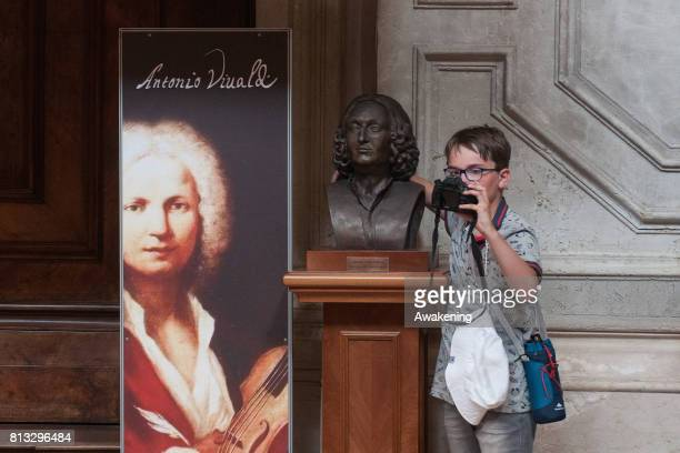 A child makes a selfie with Antonio Vivaldi statue during a visit at the Chiesa della Pietà on July 12 2017 in Venice Italy Chiesa della Pietà has...