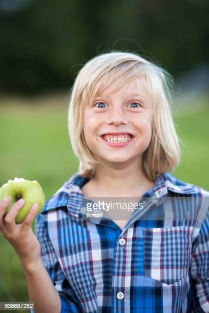 child making a face and eating green apple - menino loiro olhos azuis imagens e fotografias de stock