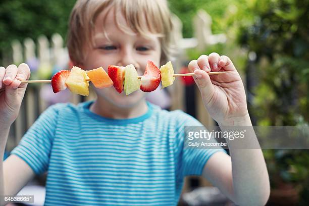 Child making a fruit kebab