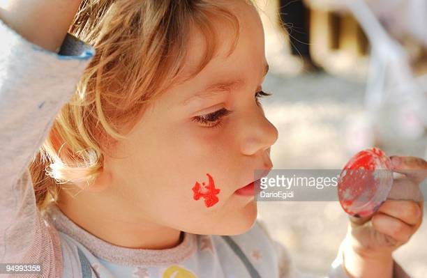 Child making up with colours for face, close-up, side view